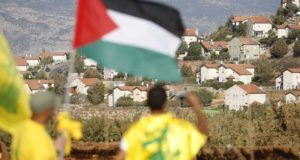 """Supporter of Lebanon's Hezbollah waves a Palestinian flag during a rally marking """"Quds Day"""" along a border fence separating Lebanon with Israel at Kfar Kila village in southern Lebanon"""