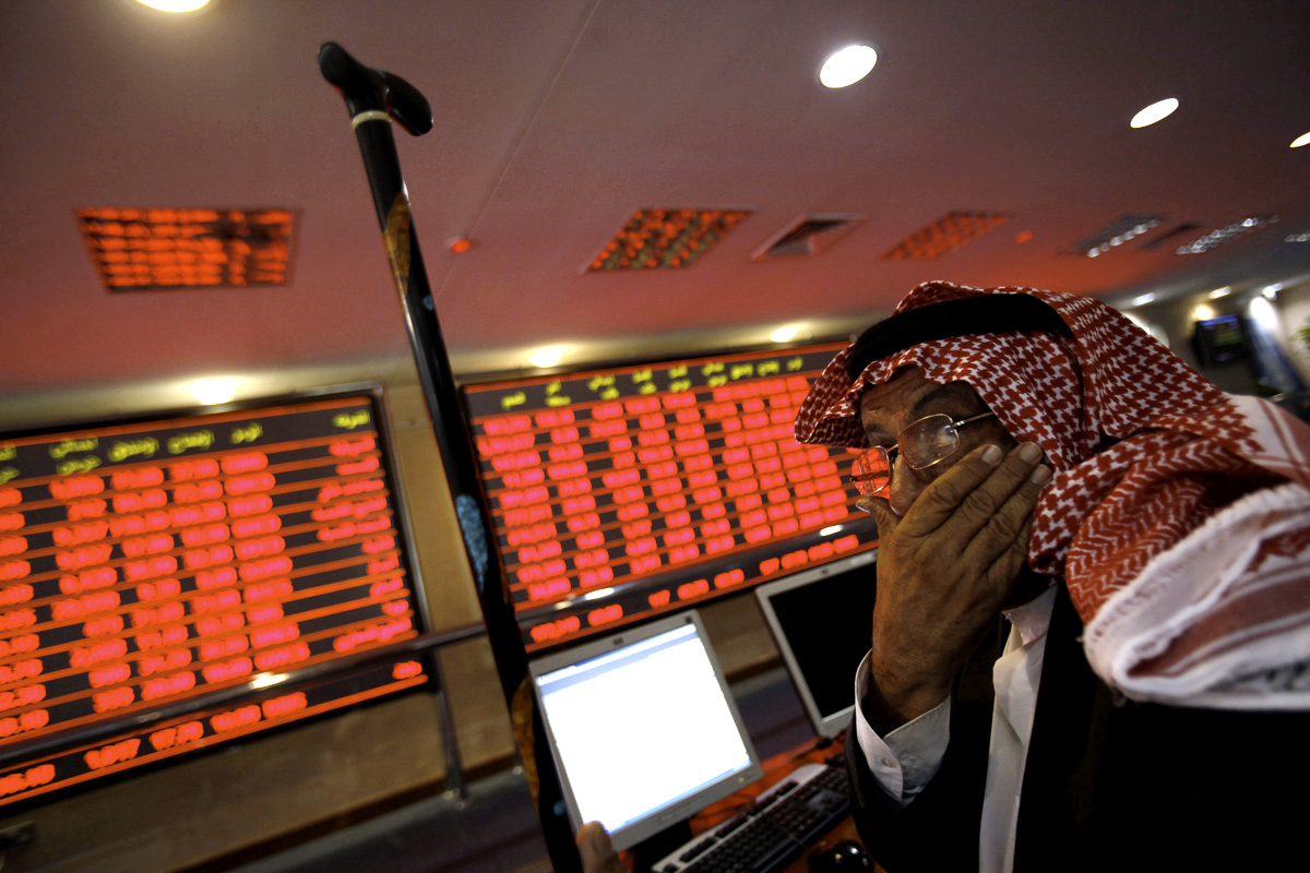 A Qatari investor follows the stock market activity at the Doha Securities Market on December 1, 2009. Qatari stocks lost a massive 8.3 percent by the close, the first day of trading after a five-day public holiday, amid worries the gas-rich Gulf state could be exposed to the Dubai debt crisis. AFP PHOTO/KARIM JAAFAR (Photo credit should read KARIM JAAFAR/AFP/Getty Images)